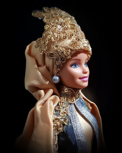 Close-up of fashion doll against black background