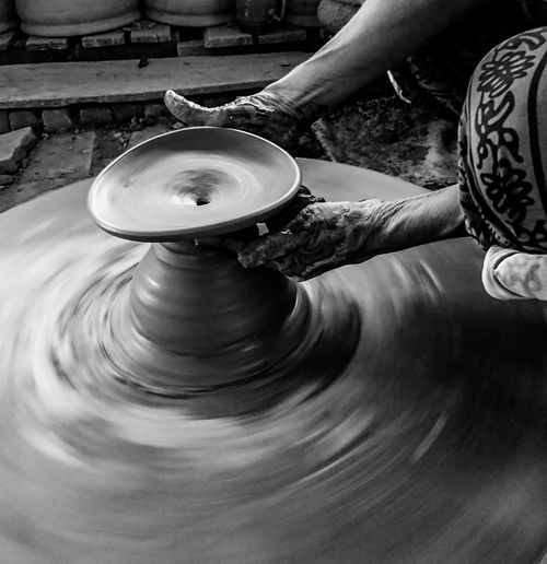 Cropped hands of worker making pottery in workshop
