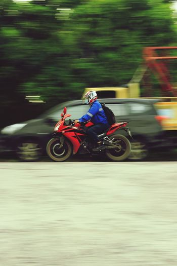 Blurred motion of man riding toy car on road