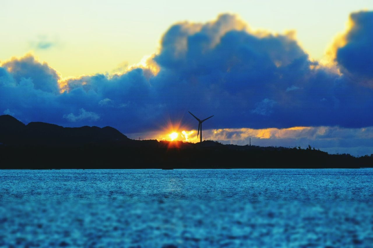 sunset, sky, beauty in nature, scenics, nature, tranquility, tranquil scene, silhouette, cloud - sky, outdoors, fuel and power generation, alternative energy, windmill, no people, wind turbine, wind power, industrial windmill, mountain, sea, water, day