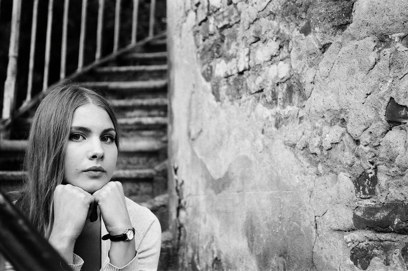 Portrait of young woman with hands on chin sitting at steps by weathered wall
