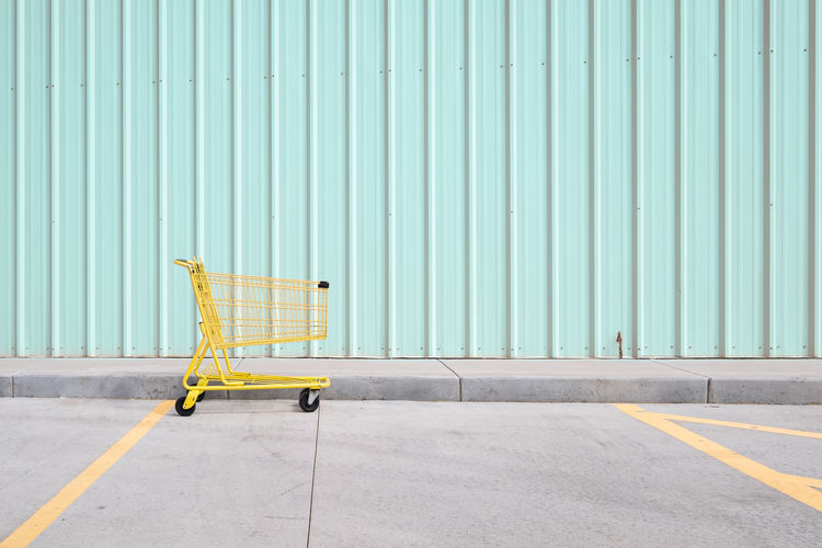 Yellow shopping cart on footpath against wall