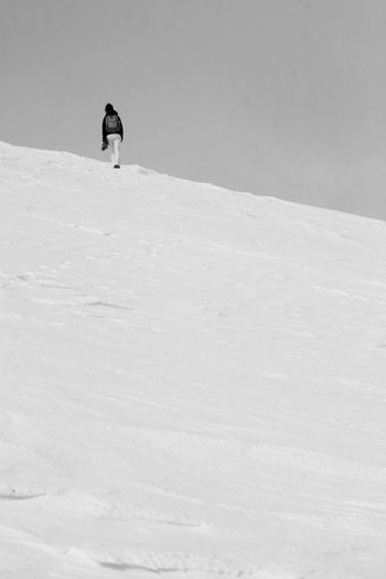 Distant view of person walking on snowy mountain against sky