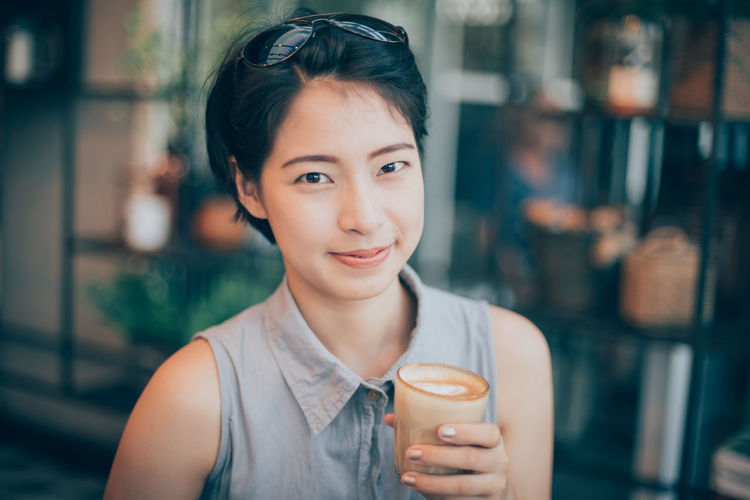 Close-up portrait of young woman drinking drink at cafe
