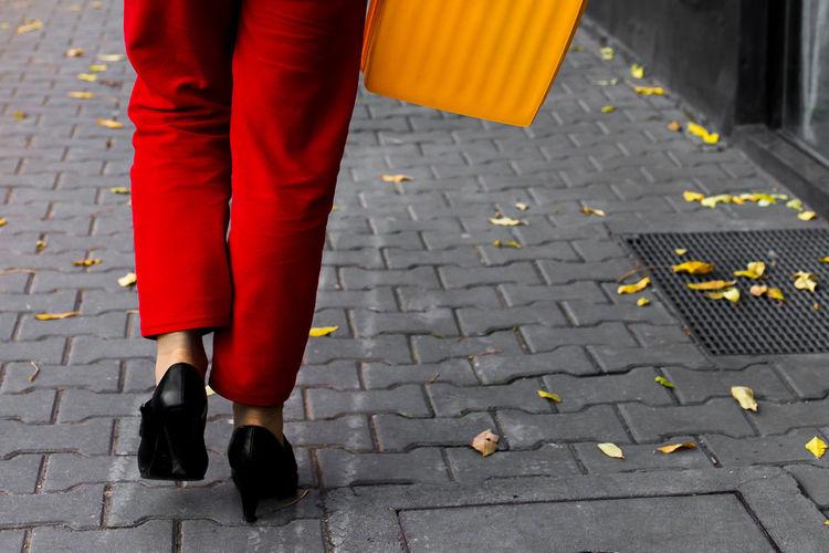 Low Section Of Woman Walking On Sidewalk