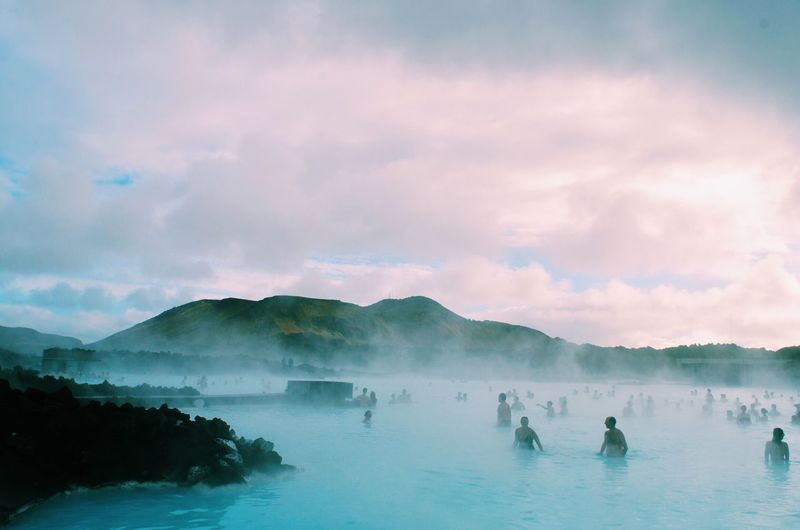 Crowd Bathing In Hot Spring Against Cloudy Sky