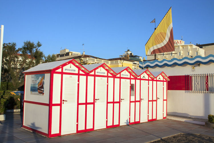 Architecture Beach Cabins Blue Building Exterior City Clear Sky Cultures Day Flag No People Outdoors Red Red Color Row House Sky Summer Travel Destinations