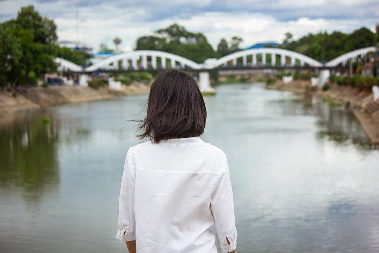 Rear view of woman standing on bridge over river