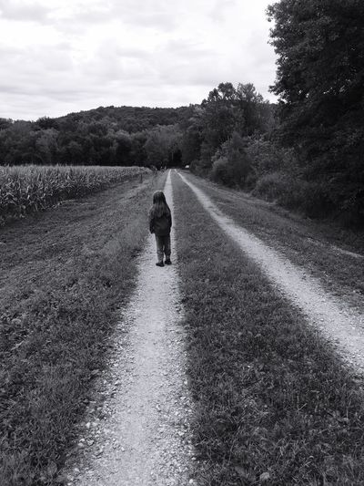 Child standing on a dirt road