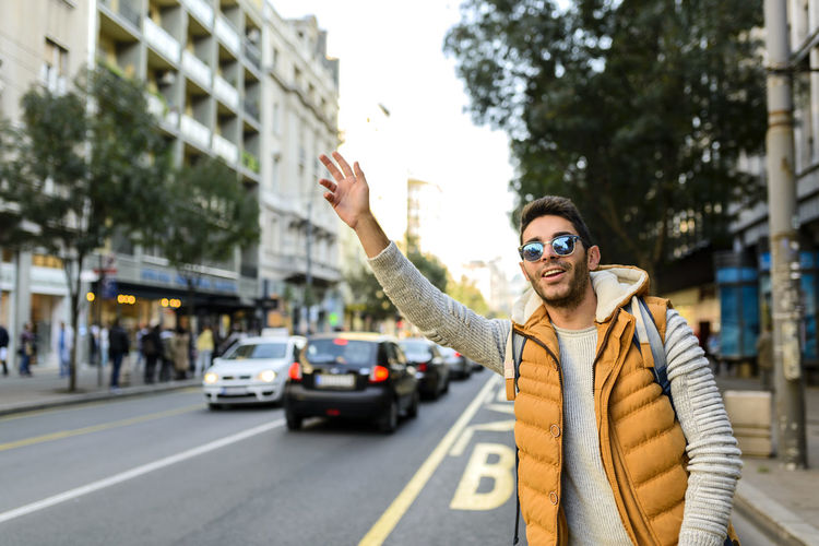 Handsome hipster with orange jacket and sunglasses stopping taxi in the city street Architecture Building Exterior Car City City Life City Street Focus On Foreground Front View Gesturing Glasses Human Arm Lifestyles Mode Of Transportation Motor Vehicle One Person Outdoors Real People Standing Street Transportation Waist Up Young Adult