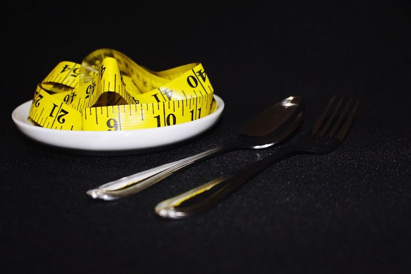 Close-up of yellow tape measure in plate by cutlery on table