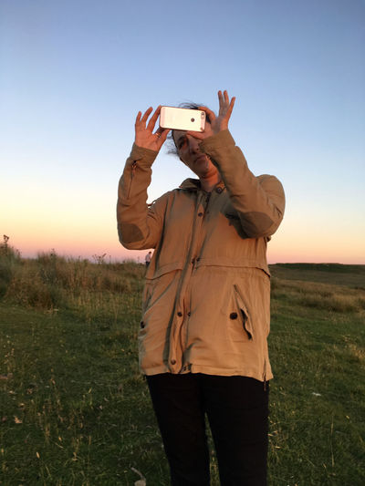 Woman photographing with mobile phone on field during sunset