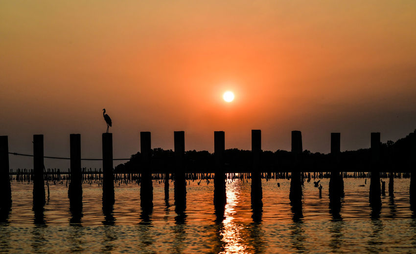 Silhouette wooden posts in sea against sky during sunset