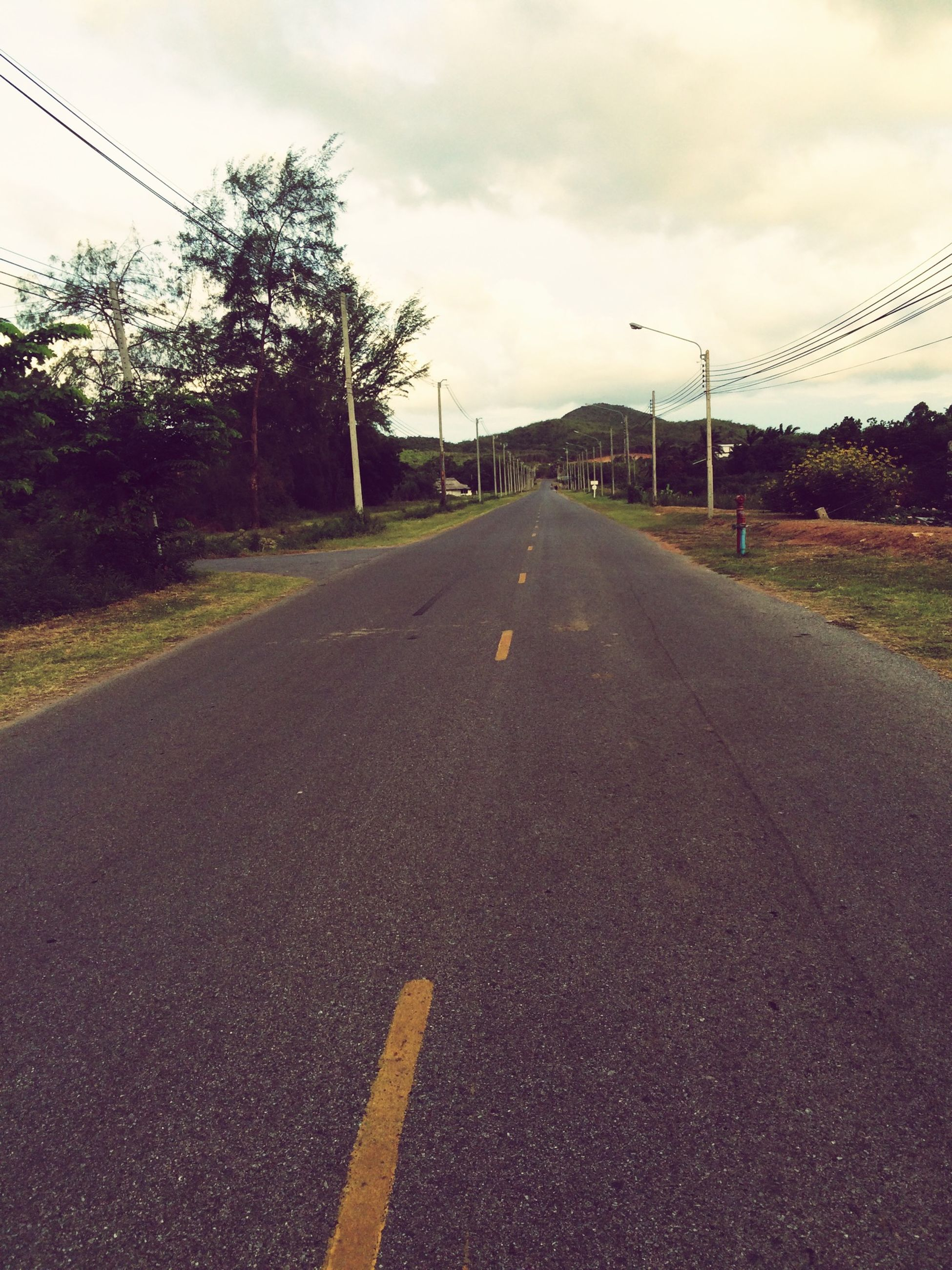 the way forward, transportation, diminishing perspective, road marking, road, sky, vanishing point, asphalt, cloud - sky, empty, country road, empty road, cloudy, surface level, cloud, street light, tree, long, street, outdoors