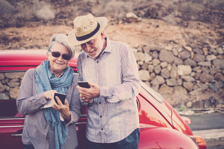 Senior couple using smart phones while standing by car