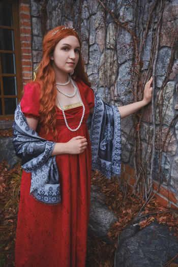 Young woman with long red hair and victorian dress near wall