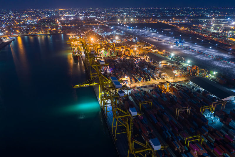 Shipping containers cargo transportation import and export international service by the sea at night