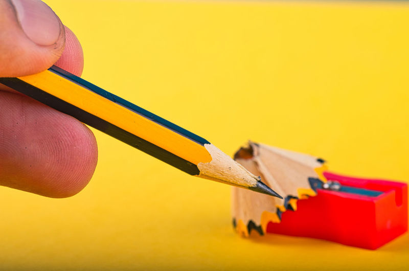 cropped hand holding graphite wooden pencil on yellow background Yellow Human Hand Hand Pencil Human Body Part Indoors  Close-up One Person Holding Studio Shot Art And Craft Wood - Material Colored Background Copy Space Craft Real People Human Finger Finger Still Life