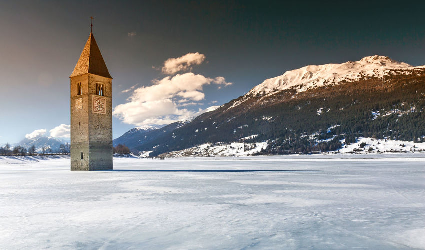Bell Tower In Frozen Lake Reschen Against Sky