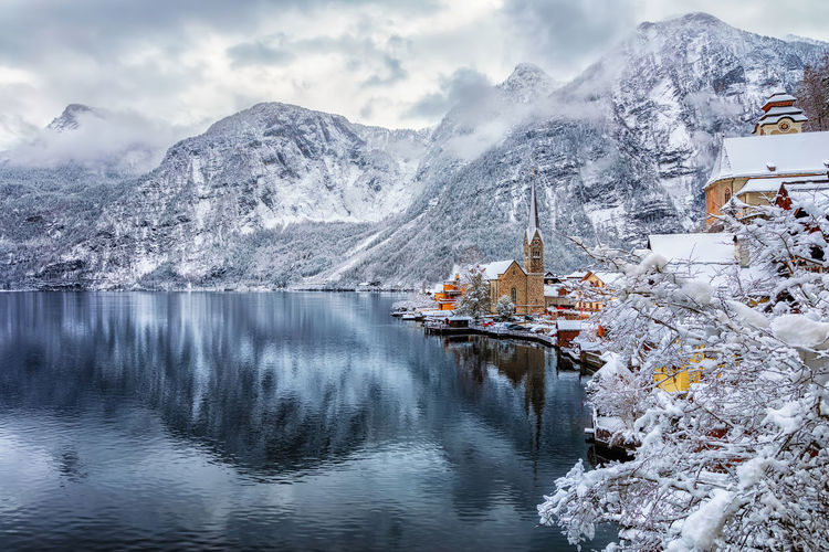 Scenic View Of Houses By Snowcapped Mountains And Lake Against Sky