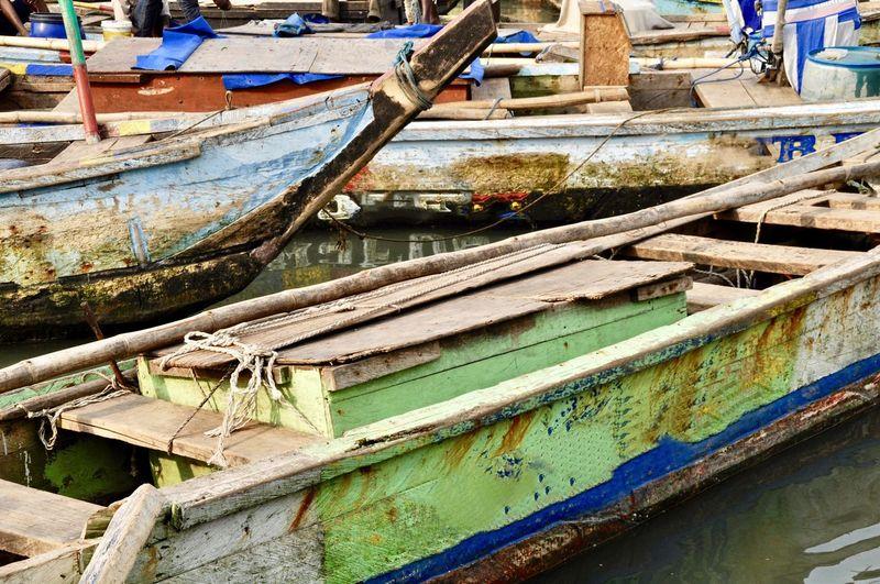 Abandoned boats moored at harbor
