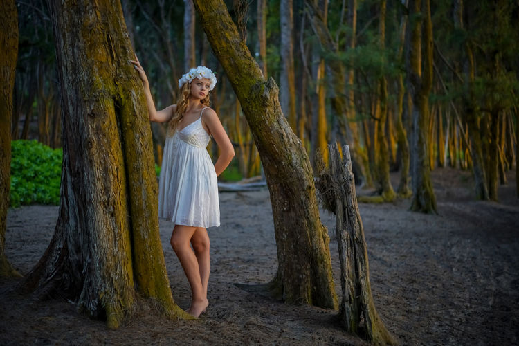 Woman standing by tree trunk