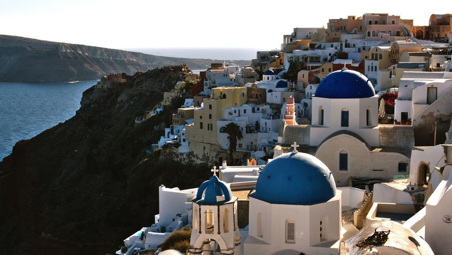 Buildings by sea at santorini on sunny day