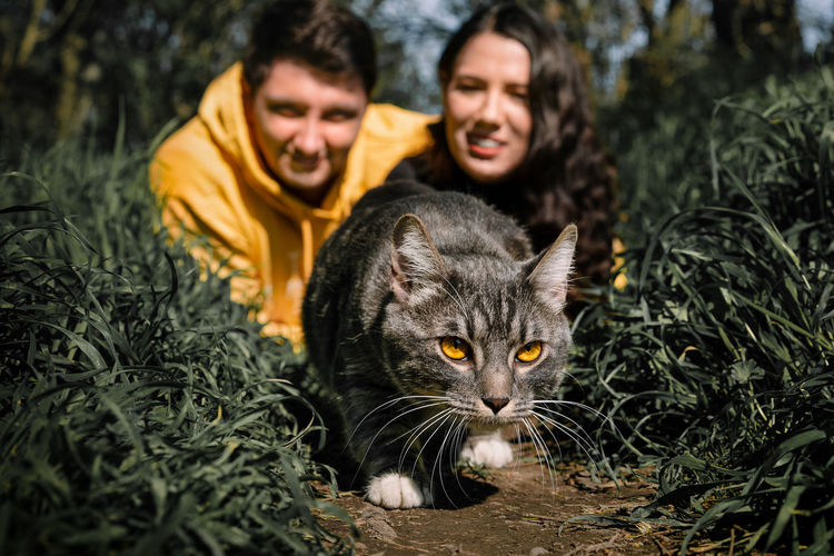 Portrait of man and cat by plants