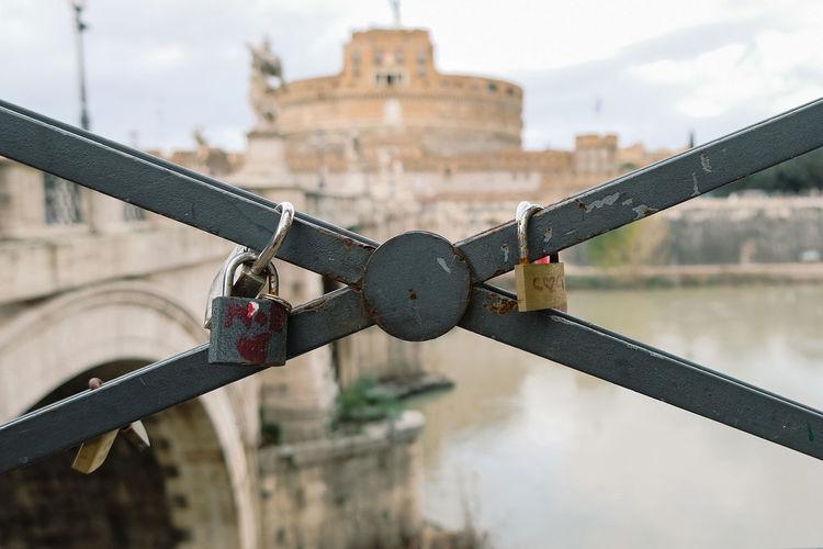 Close-up of padlocks on bridge against sky