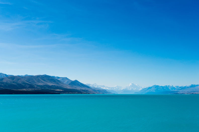 A turquoise blue lake with snow covered mountains in the distance Beauty In Nature Blue Coastline Day Distant Majestic Mountain Mountain Range Natural Landmark Nature Non-urban Scene Outdoors Physical Geography Remote Scenics Sea Seascape Sky Tourism Tranquil Scene Tranquility Vibrant Color Water Water Surface Waterfront