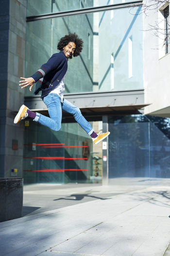 Portrait Of Man Jumping Against Building In City