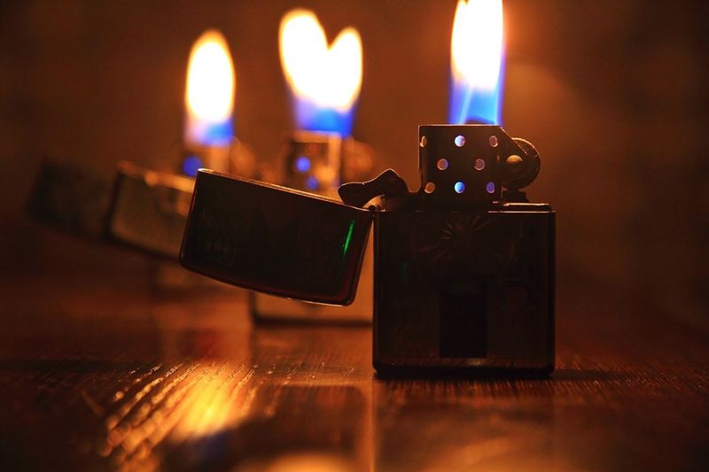 Close-up of burning zippo lighters on table