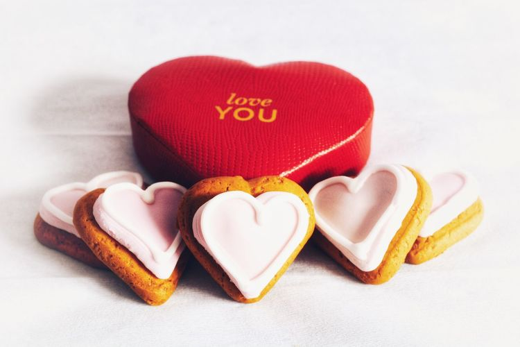 Heart shaped gingerbread cookies with pink icing and a red heart shaped box with Love You in gold White Background Pink Icing Gingerbread Cookie Heart Shape Biscuits Cookies Sweet Food Pink Hearts Romantic Valentine's Day  Heart Shape Love Still Life Romance No People Indoors  Red Close-up White Background