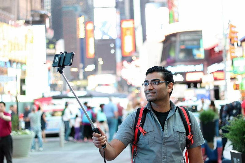 Happy handsome young man taking a selfie in a busy urban city street America Billboard BookBag College Grey Indian Light New York New York City Outdoors Photography Selfie Selfie Stick Smile Smiling Smiling Face Student Students Times Square Times Square NYC Tourism Tourist Travel Trip Vacations