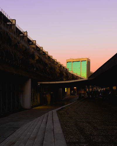 Illuminated footpath amidst buildings against clear sky at sunset