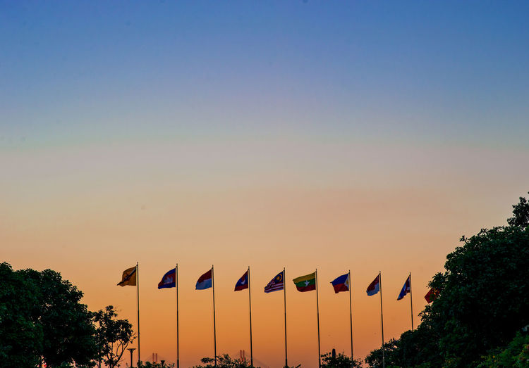 Multi colored flags against clear sky during sunset