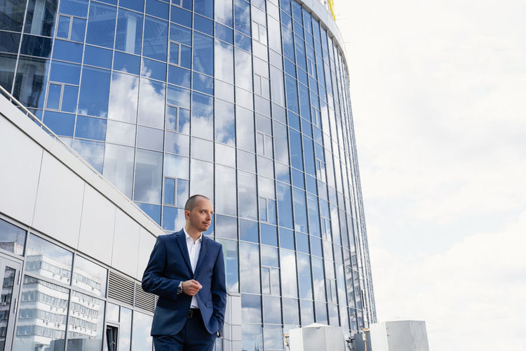 Low angle view of man standing on glass building