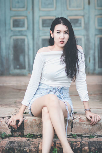 Young Adult Lifestyles One Person Looking At Camera Leisure Activity Young Women Portrait Real People Beautiful Woman Hair Hairstyle Women Sitting Architecture Casual Clothing Long Hair Day Full Length Fashion Outdoors Shorts Teenager Asian Teen Asian Woman