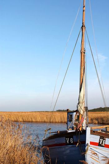 Sailboat moored at riverbank against sky