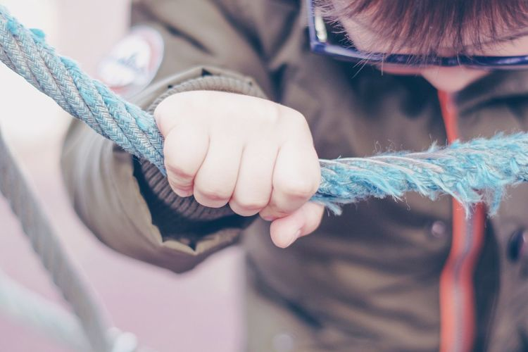 Close-up of boy holding rope