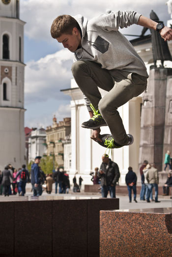 Young man jumping over seat in city