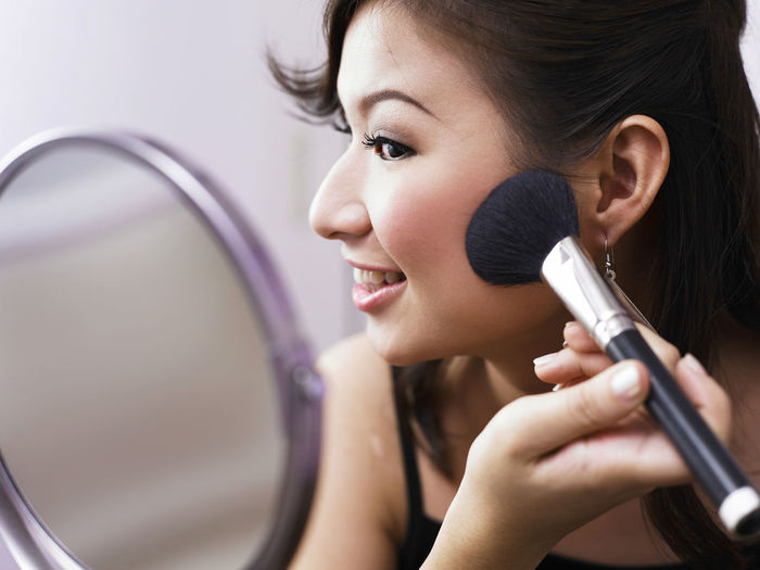Close-Up Of Smiling Young Woman Applying Make-Up With Brush