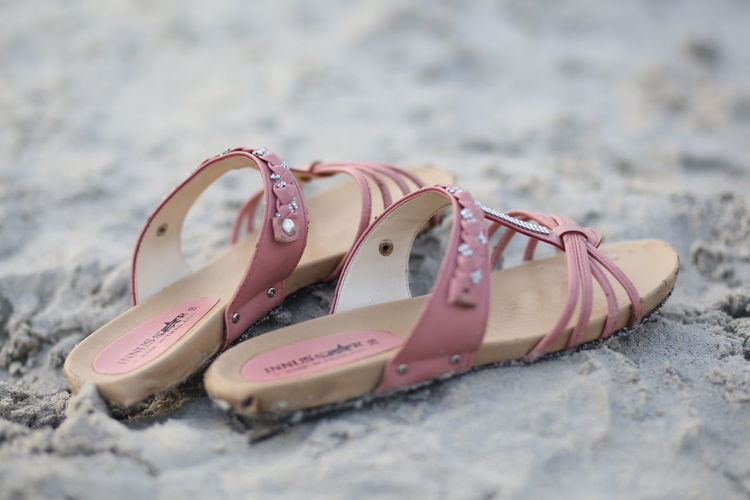 Close-up of footwear on sand at beach