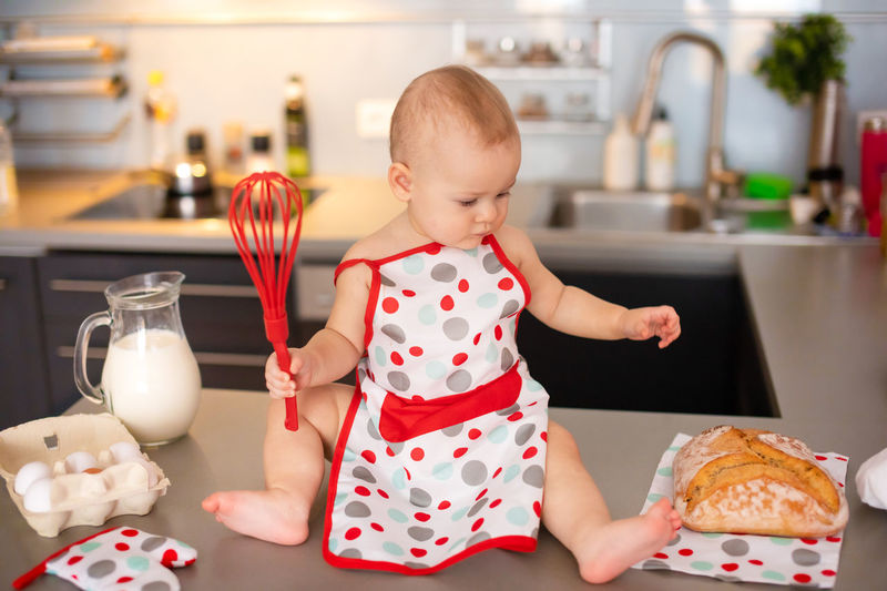 Full length of cute girl holding food at home