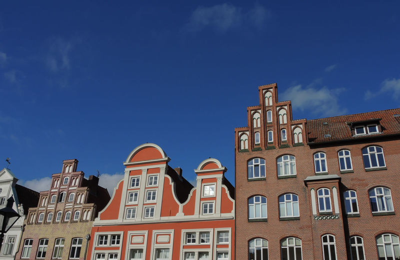 Low Angle View Of Buildings In Town Against Blue Sky