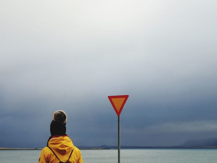 Rear view of woman in warm clothing standing by signboard at beach against cloudy sky