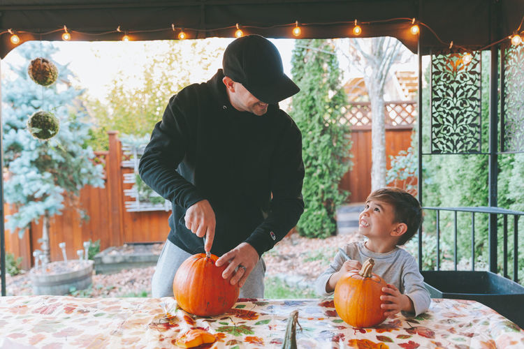 Father and son cutting pumpkin on table