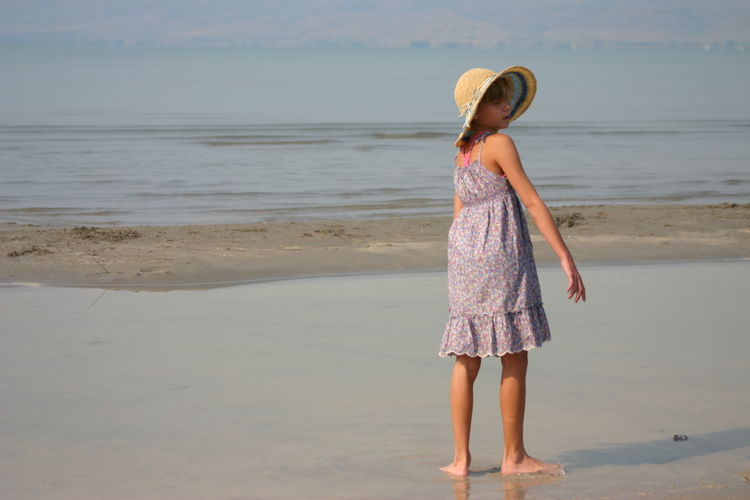Rear view of girl standing on shore