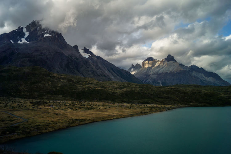 cuerno`s and torres del Paine at sunset Beauty In Nature Cloud - Sky Day Environment Lake Landscape Mountain Mountain Peak Mountain Range Nature No People Outdoors Scenery Scenics - Nature Sky Snow Snowcapped Mountain Water Wilderness