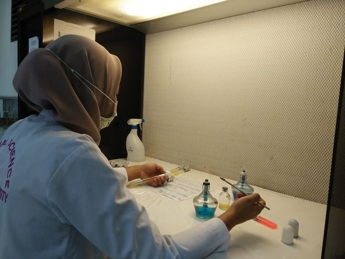 Rear view of scientist working at lab